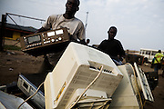 A man loads electronics destined for junk on a cart at the Agbogboloshie market in Accra, Ghana on Tuesday August 12, 2008.