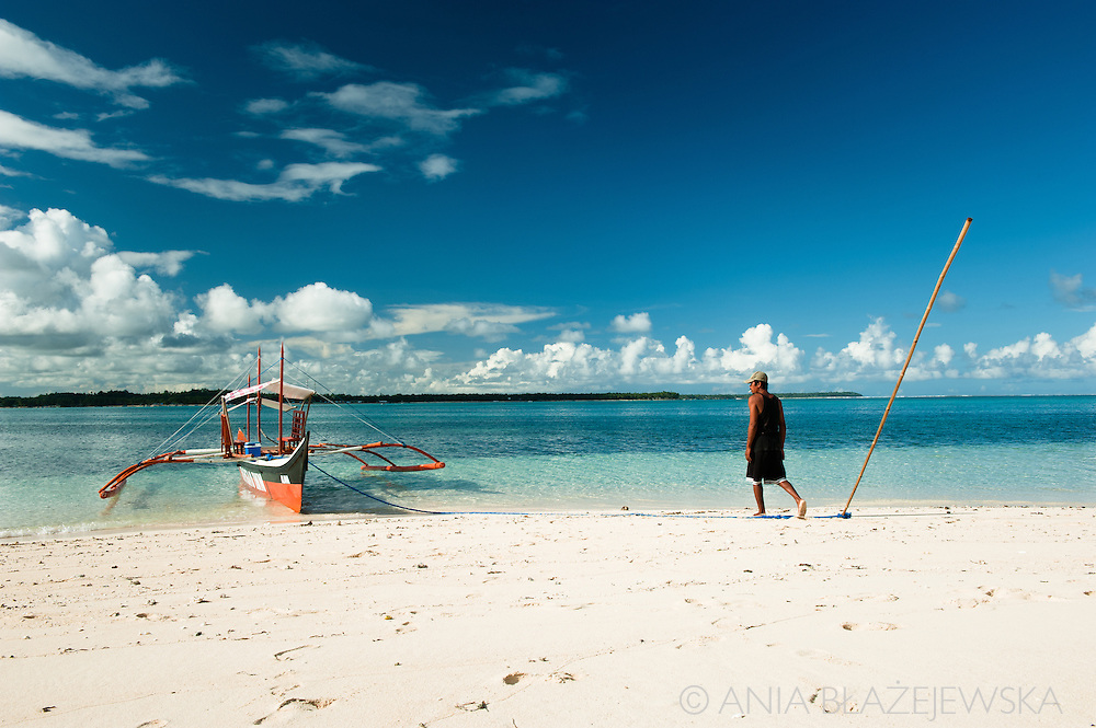 Philippines, Siargao. Bangka and its boat driver on the beach on Guyam Island, one of the tropical island of the archipelago.