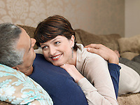 Smiling couple relaxing on sofa in living room