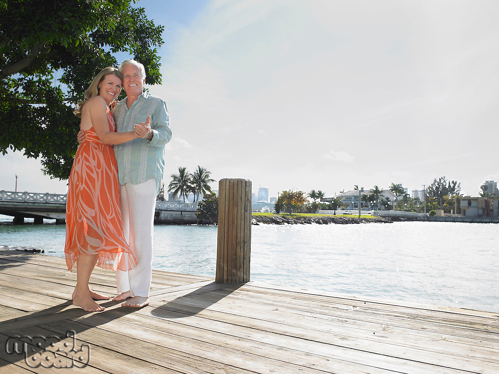 Couple embracing standing on pier portrait