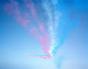 Flying overhead into the distance, Hawk jet aircraft of the elite 'Red Arrows', Britain's prestigious Royal Air Force aerobatic team, leave behind a trail of red, white and blue smoke in the clear skies above RAF Akrotiri, Cyprus. Completing their off-season training, the team put the finishing touches to their display routine every Spring on the Mediterranean island where they perfect new manoeuvres. The sky is empty but as the light wind blows across the airfield, the remainder of the tapering coloured smoke (a mixture of vegetable dye and 'derv' - diesel fuel), blends together like a patriotic ribbon to make a haze of soft spectrum in the correct order of the United Kingdom's flag, and which becomes ever-sharper as the viewer looks towards the distant aircraft. They fly past, bend to the left and climb to a higher altitude, ready for their next formation.