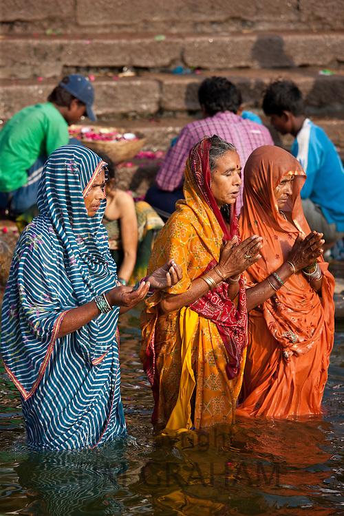 Indian Hindu pilgrims bathing and praying  in The Ganges River at Dashashwamedh Ghat in Holy City of Varanasi, India