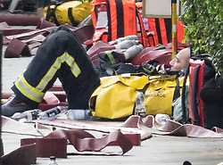 © Licensed to London News Pictures. 06/06/2018. London, UK. A fire fighter rest amongst fire hoses on the pavement outside the Mandarin Oriental hotel after a fire. Fifteeen fire engines and 97 firefighters and officers have been called to a fire believed to be at the Mandarin Hotel in Kightsbridge. Photo credit: Peter Macdiarmid/LNP