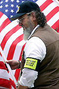 Member of the Patriot Guard Riders holding US flags during the funeral service of Sgt. Ian T. Sanchez, in Staten Island, NY., on Tuesday, June 27, 2006. Sgt. Sanchez, a 26-year-old American serviceman was killed by a roadside bomb in the Pech River Valley, Afghanistan. The Patriot Guard Riders is a diverse amalgamation of riders from across the United States of America. Besides a passion for motorcycling, they all have in common an unwavering respect for those who risk their lives for the country's freedom and security. They are an American patriotic group, mainly but not only, composed by veterans from all over the United States. They work in unison, calling upon tens of different motorcycle groups, connected by an internet-based web where each of them can find out where and when a 'Mission' is called upon, and have the chance to take part. This way, the Patriot Guard Riders can cover the whole of the United States without having to ride from town to town but, by organising into different State Groups, each with its own State Captain, they are still able to maintain strictly firm guidelines, and to honour the same basic principles that moves the group from the its inception. The main aim of the Patriot Guard Riders is to attend the funeral services of fallen American servicemen, defined as 'Heroes' by the group,  as invited guests of the family. These so-called 'Missions' they undertake have two basic objectives in particular: to show their sincere respect for the US 'Fallen Heroes', their families, and their communities, and to shield the mourners from interruptions created by any group of protestors. Additionally the Patriot Guard Riders provide support to the veteran community and their families, in collaboration with the other veteran service organizations already working in the field.   **ITALY OUT**