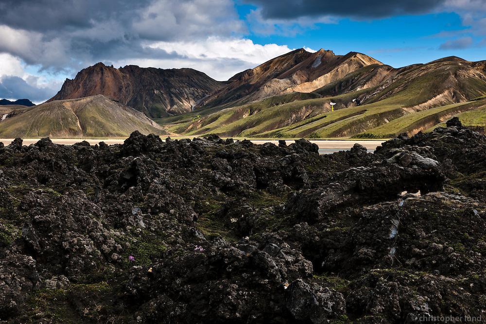Norðurnámshraun lavafield near Landmannalaugar, Iceland. Mount Norðurbarmur and Kýlingaskarð in background. Norðurnámshraun við Landmannalaugar. Norðurbarmur og Kýlingaskarð í baksýn.
