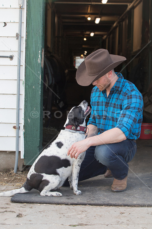 cowboy with a dog by a barn