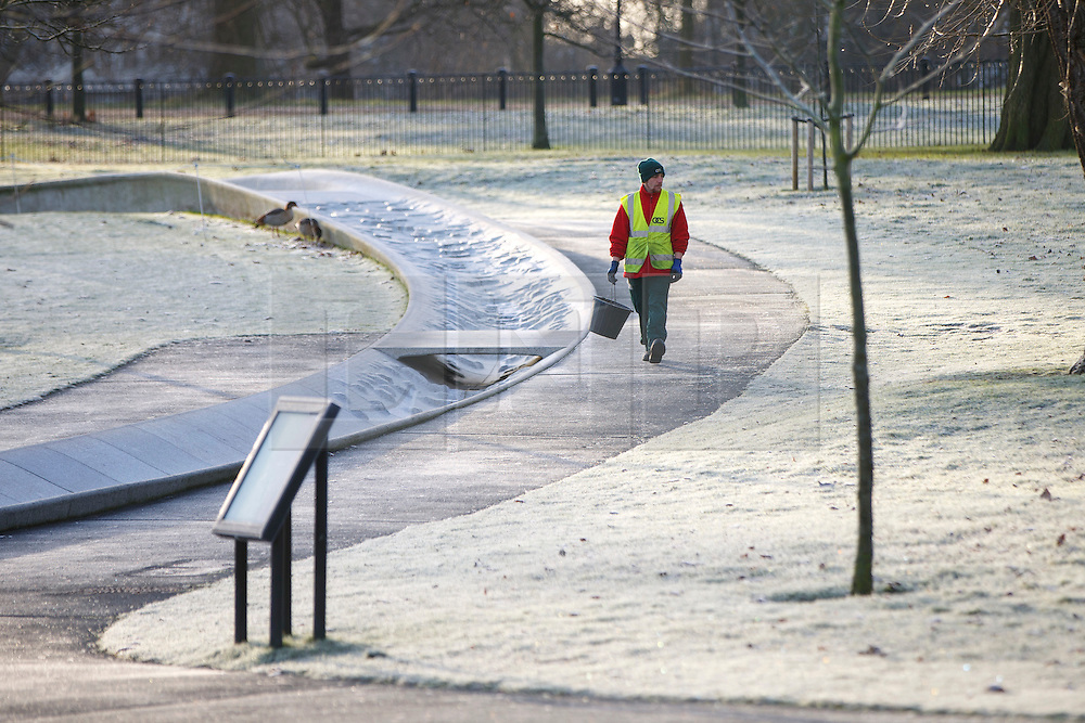 © Licensed to London News Pictures. 03/01/2017. London, UK. A cleaner walks through Diana, Princess of Wales Memorial Fountain in Hyde Park, London on a frosty morning as temperatures in the capital drop below zero celsius on Tuesday, 3 January 2017. Photo credit: Tolga Akmen/LNP