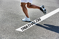 Man running on white line with triathalon sign