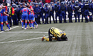 BSC Young Boys player Seydou Doumbia kneels on the ground disappointed, while the police secures the pitch and FC Basel players celebrate their victory in the Super League (National League A) soccer match between BSC Young Boys (YB) and FC Basel (FCB) at the Stade de Suisse stadium in Bern, Switzerland, Sunday, Mai 16, 2010. FC Basel have won the Swiss football championship beating Young Boys of Bern 2-0 in the last match of the season. (Photo by Patrick B. Kraemer / MAGICPBK)