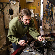Backyard mechanic at work on his car in the garage. Home business, DIY