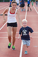 Middletown, New York - A teenage girl helps a young boy finish a race during the Twilight Track and Field Series run by the Middletown High School Varsity track program on July 22, 2014.
