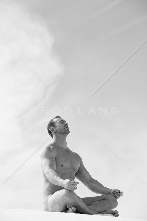 nude man mediating outdoors