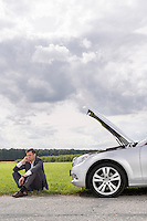 Full length of unhappy young businessman sitting by broken down car at countryside