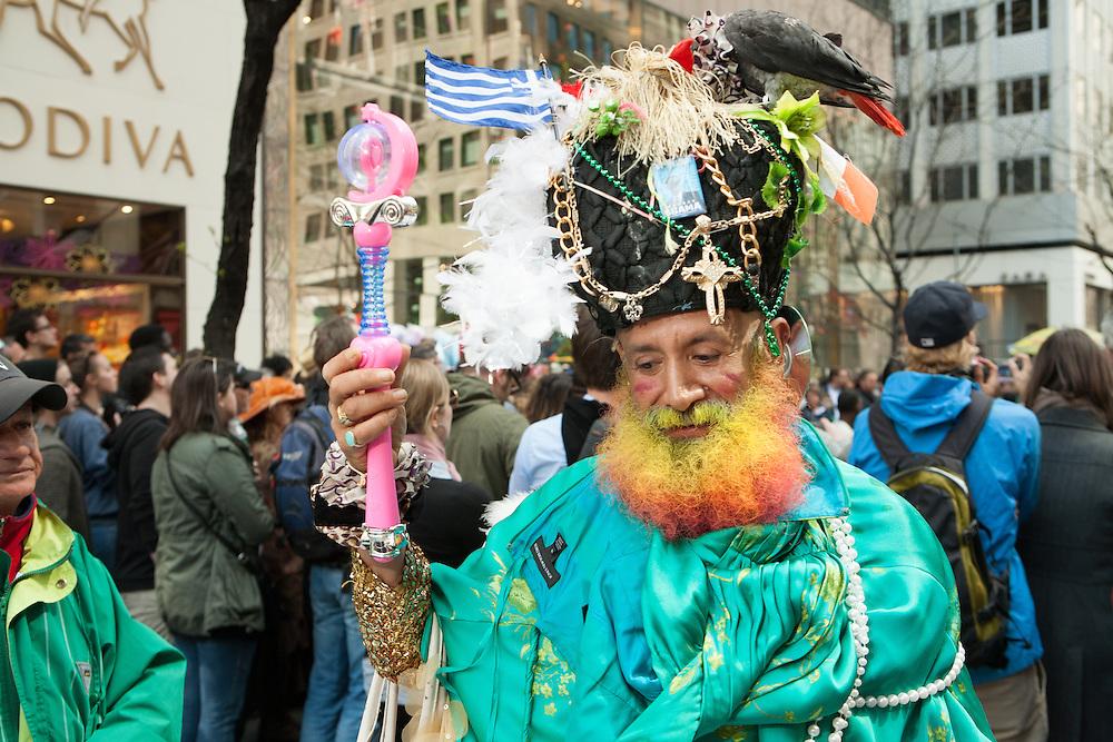 A man with a multi-colored beard, an aqua cape, and a large headdress with a live bird.