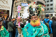 A man with a multi-colored beard, an aqua cape, and a large headdress with a live bird.