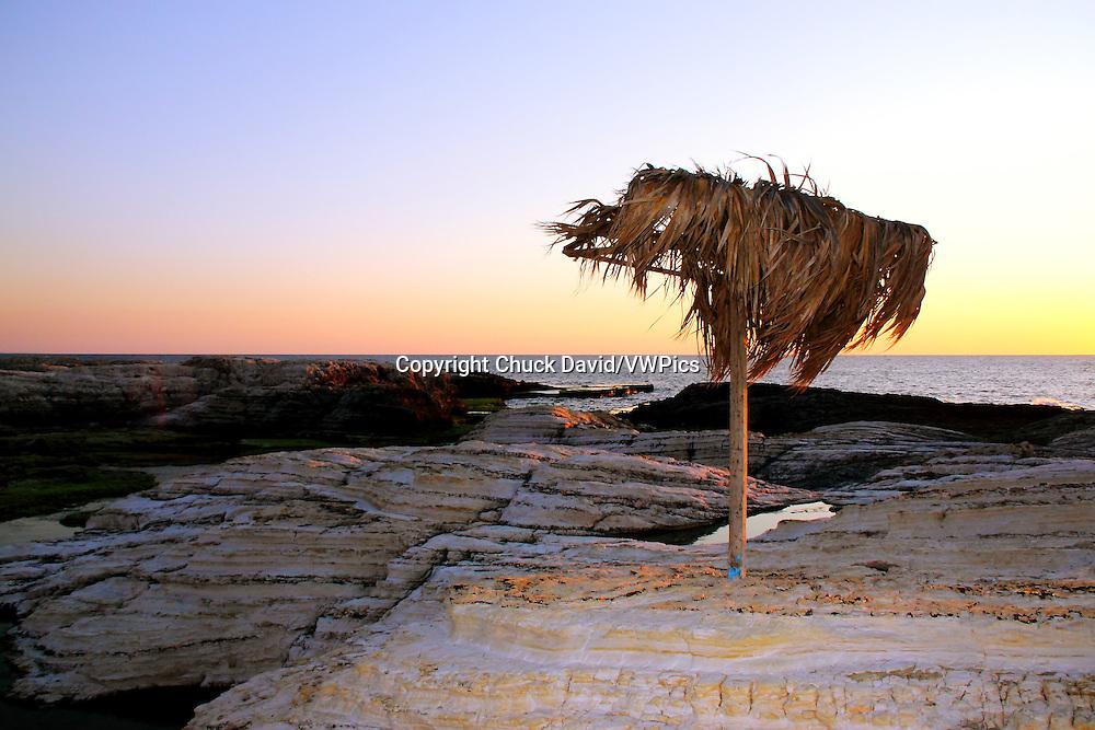 Sunset on Beirut's rocky Mediterranean shoreline, Lebanon.