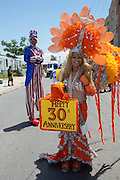 "A woman carries a ""Happy 30th Anniversary: sign while a man on stilts in an Uncle Sam costume looks on."