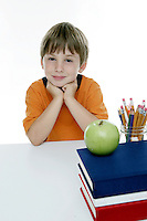 20 July 2008:  Back to School with grammar school Lytle brothers in Huntington Beach, CA.  Matthew Lytle age 6 sitting at a desk with school books, a green apple and pencils looking at the camera in the studio on white seamless paper silo.