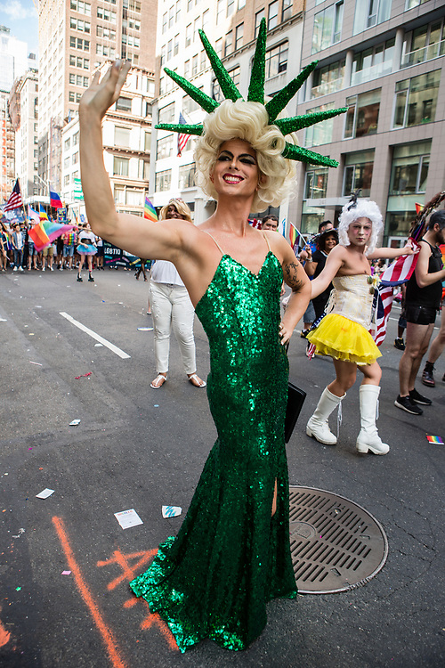 New York, NY - 25 June 2017. New York City Heritage of Pride March filled Fifth Avenue for hours with groups from the LGBT community and it's supporters. A drag queen wear a green sequined gown and a crown like the Statue of Liberty's.
