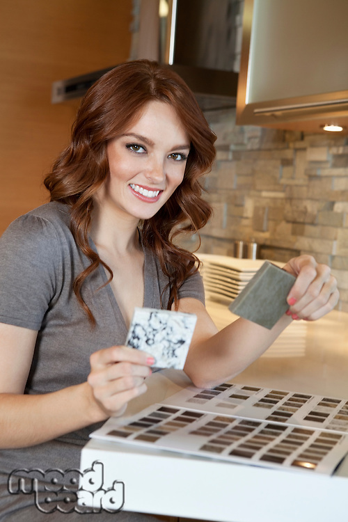 Portrait of a happy young woman with tile samples in model home
