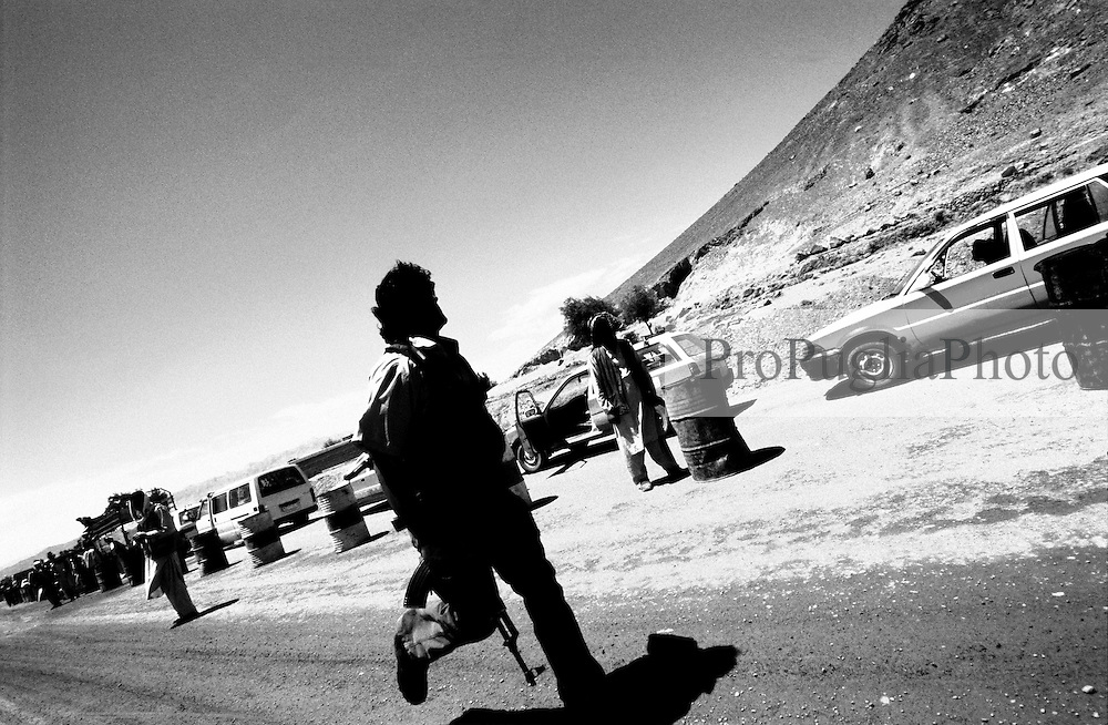 AFGHANISTAN, 10 August 2005...On the road from Kabul to Gardez a private security guard, holding an AK-47, run towards his car.
