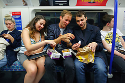 © Licensed to London News Pictures. 20/08/2016. London, UK. Tube passengers eating fast food products whilst travelling on the night tube service of Victoria line in London for the first time on 20 August 2016. Transport for London started a 24-hour Tube service on Victoria and Central lines as demand has soared over recent years, with passenger numbers on Friday and Saturday nights up by around 70 per cent since 2000. The plan was announced in November 2013 and intended to begin in September 2015, but strikes over pay delayed the start by nearly another year. Photo credit: Tolga Akmen/LNP