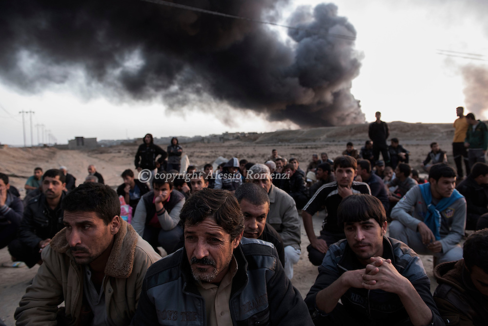 Iraq, Qarayya: Newly displaced sit at a check point in Qayyara as they wait to get back their document after being identified on October 31, 2016. Alessio Romenzi