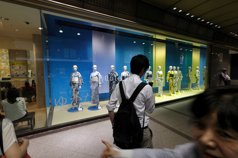people walking past a window display of mannequins wearing modern Yukata style kimono