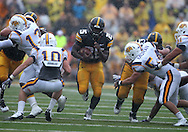 September 3, 2011: Iowa Hawkeyes running back Mika'il McCall (25) runs through a hole as Tennessee Tech Golden Eagles cornerback Taylor Hennigan (10) closes in during the first half of the game between the Tennessee Tech Golden Eagles and the Iowa Hawkeyes at Kinnick Stadium in Iowa City, Iowa on Saturday, September 3, 2011. Iowa defeated Tennessee Tech 34-7 in a game stopped at one point due to lightning and rain.