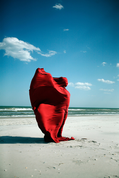 A woman wrapped in a red cloth stands on a beach, the wind pressing the material into her shape.
