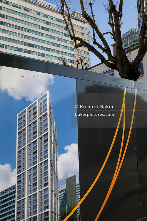 A graphic showing a future apartment high-rise to be built by housing trust 'Notting Hill Genesis', is seen on the construction site hoarding, beneath older, ugly architecture, on 21st January 2020, in Croydon, London, England.
