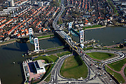Nederland, Zuid-Holland, Capelle aan den IJssel, 20-03-2009; stormvloedkering in de Hollandsche IJssel. Bij storm en dreigend hoog water wordt een van de twee schuiven naar beneden gelaten, de tweede schuif dient al reserve. De scheepvaart kan de gesloten kering paseren via de naastgelegen schutsluis. Boven in beeld Krimpen aan den IJssel.   .De stormvloedkering maakt deel uit van de Deltawerken en is als eerste voltooid in 1958. Ten tijde van De Ramp - watersnood 1953 - werd het zeewater door de storm opgestuwd en dreigde de verzwakte rivierdijken in het achterland het te begeven waardoor grote van het laag gelegen westen van Nederland ondergelopen zouden zijn..Netherlands, Capelle at the river IJssel, near Rotterdam: storm surge barrier, protects the highly populated western part of Holland, which lies below sea level. In case of storm and threat of high water, one of the two doors is lowered into the river (the second door is a spare one). The lock next to the barrier allows shipping when the barrier is closed.Swart collectie, luchtfoto (toeslag); Swart Collection, aerial photo (additional fee required).foto Siebe Swart / photo Siebe Swart