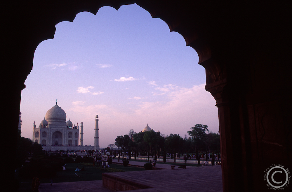 The Taj Mahal at sunset, framed by one of the Arabic style doorways in the courtyard.