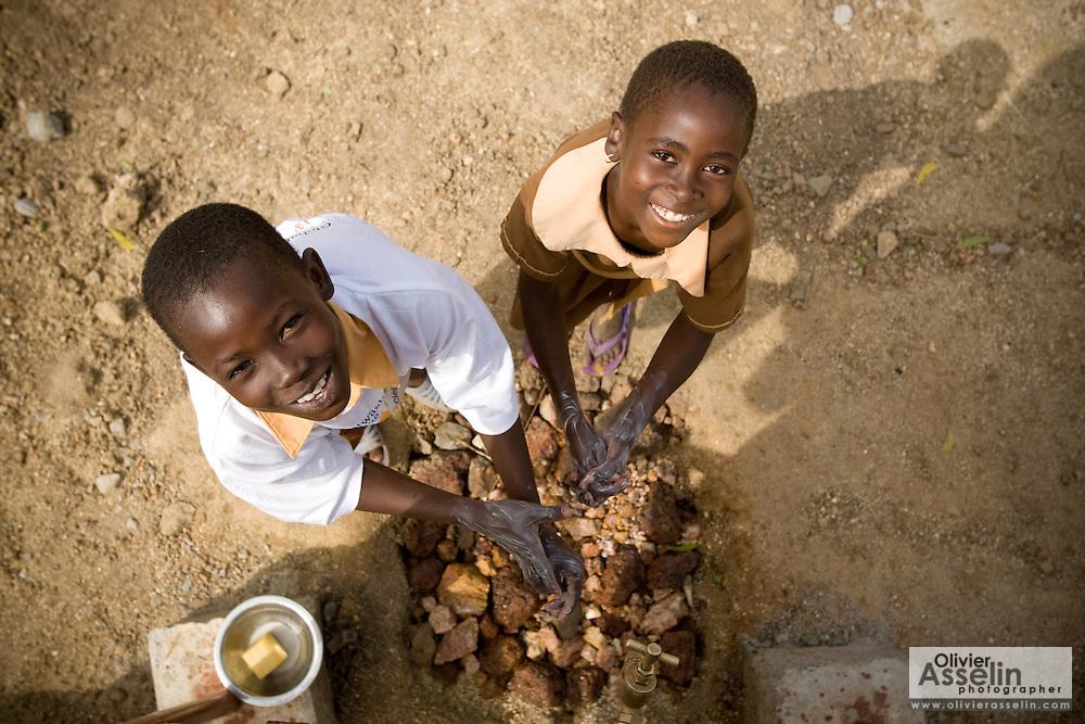 Children in school uniforms washing hands after using a latrine.Northern Ghana, Wednesday November 12, 2008.