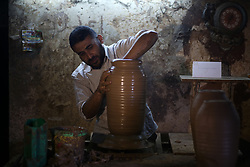 September 7, 2017 - Gaza, gaza strip, Palestine - A Palestinian man, uses a pottery wheel to construct a clay vessel, at the oldest pottery workshop in Gaza City, 07 September 2017. Pottery is an ancient and traditional craft in Gaza. Local workshops usually produce products such as bowls, pitchers, flower pots, and vases, including a big black pottery vessel known as 'al-Qedra' that is used for cooking a traditional Gazan meal made out of rice, meat, garlic and onions. (Credit Image: © Majdi Fathi/NurPhoto via ZUMA Press)