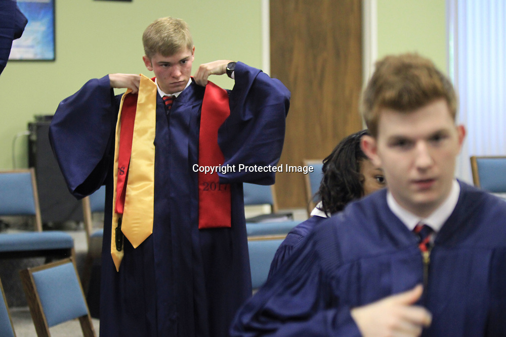 BJ Simmons adjusts his sash as he gets ready to graduate with his TCPS classmates Saturday afternoon at West Jackson Street Baptist Church in Tupelo,
