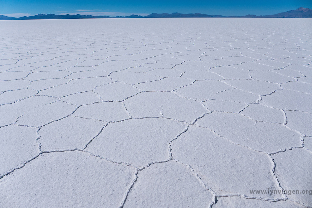 Salar de Uyuni is the world's largest salt flat at 10,582 square kilometers (4,086 sq mi). It is located in the Daniel Campos Province in Potos&iacute; in southwest Bolivia, near the crest of the Andes and is at an altitude of 3,656 meters (11,995 ft) above sea level.<br /> <br /> The Salar was formed as a result of transformations between several prehistoric lakes. It is covered by a few meters of salt crust, which has an extraordinary flatness with the average altitude variations within one meter over the entire area of the Salar. The crust serves as a source of salt and covers a pool of brine, which is exceptionally rich in lithium. It contains 50 to 70% of the world's lithium reserves, which is in the process of being extracted. The large area, clear skies, and exceptional flatness of the surface make the Salar an ideal object for calibrating the altimeters of Earth observation satellites.