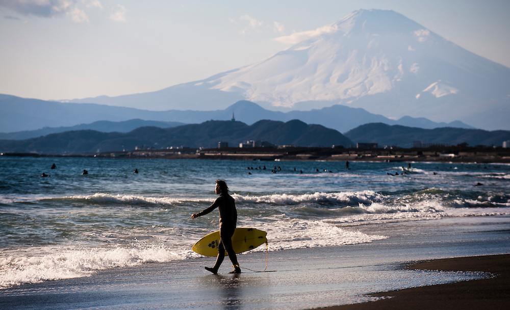 A surfer walks towards the waves at Shonan Beach with Mt. Fuji in the background.