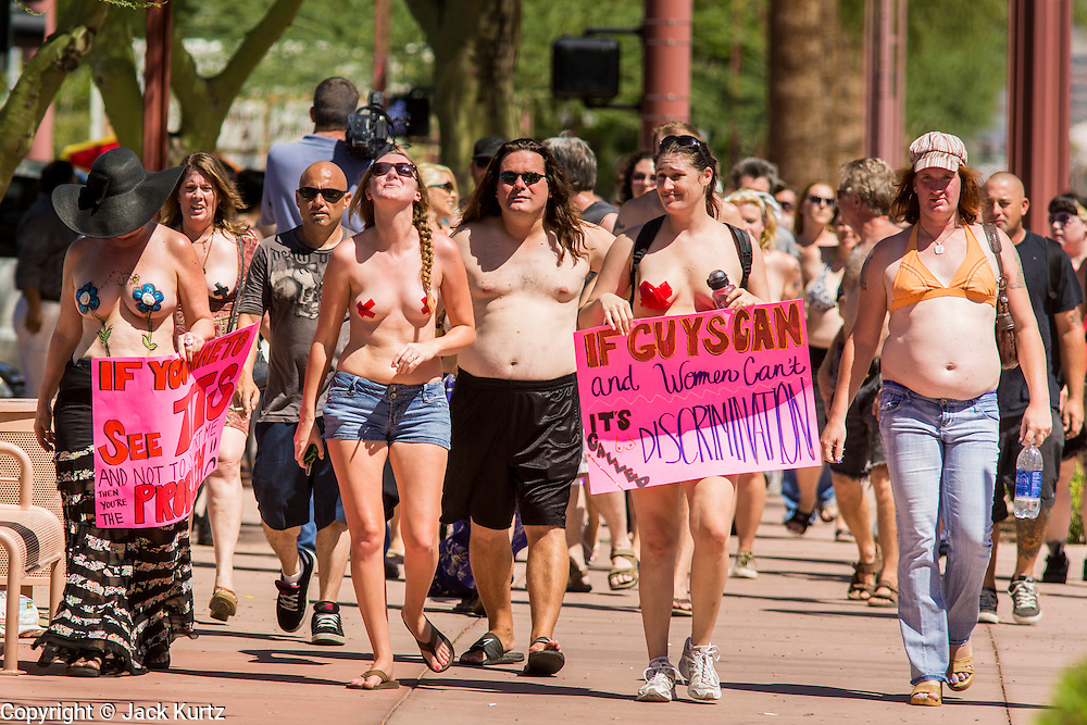 26 MARCH 2012 - PHOENIX, AZ:  CHRISTI, left, JENNA DUFFY and KELLY CAYE lead a march of topless women and men in Phoenix. About 40 people marched through central Phoenix Sunday to call for a constitutional amendment to give women the same right to go shirtless in public that men have. The Phoenix demonstration was a part of a national Topless Day of Protest. Phoenix prohibits women from going topless in public so protesters, women and men, covered their nipples and areolas with tape. The men did it to show solidarity with the women marchers.   PHOTO BY JACK KURTZ
