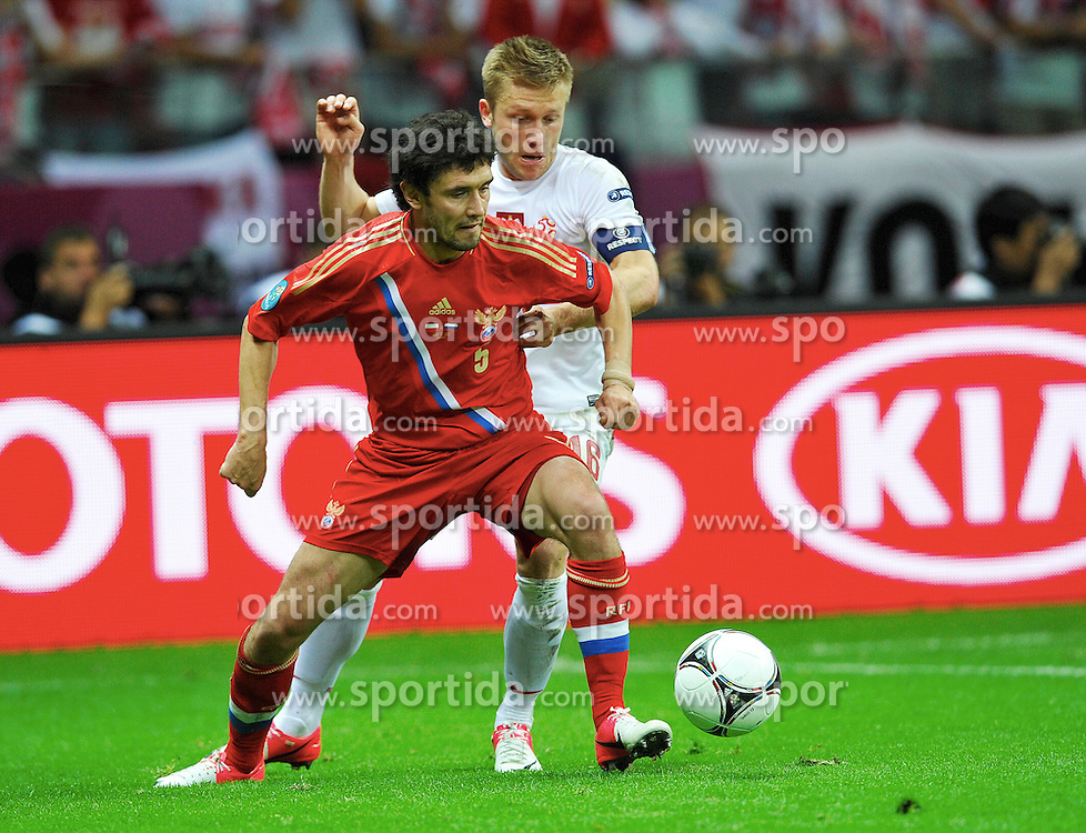 Warsaw 12/06/2012.POLAND, WARSAW .Yuri Zirkhov of Russia fights for the ball with Kuba Blaszczykowski of Poland during the Euro 2012 football championships match Poland vs. Russia, on June 12, 2012 at the National Stadium in Warsaw. .Photo by: Piotr Hawalej / WROFOTO