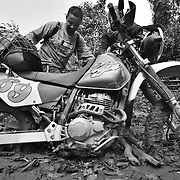 Motorbike tour guide Digby Greenhalgh tries to extricate himself from a mud pit on the Ho Chi Minh Trail, Laos.