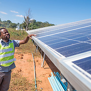 CAPTION: Tsungai checks a solar panel that forms part of the Kufandada River Protection and Irrigation Scheme Project. The electricity generated by the project will power the irrigation system and also provide power to the Bikita Rural Hospital. LOCATION: Near Bikita Rural Hospital, Bikita District, Masvingo Province, Zimbabwe. INDIVIDUAL(S) PHOTOGRAPHED: Tsungai Mavambe.