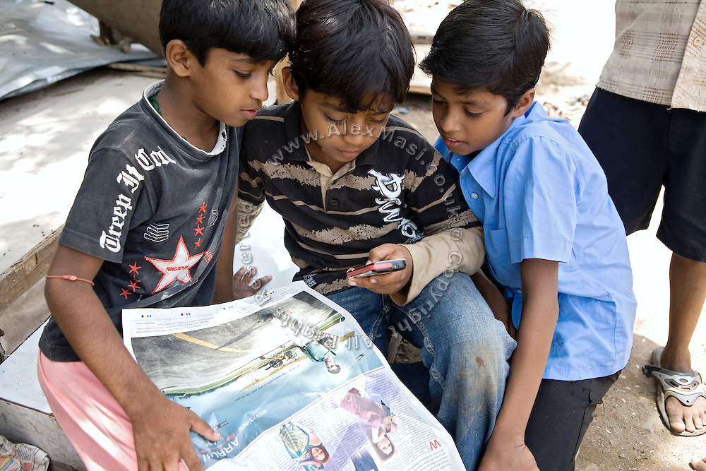 Azharuddin Ismail, 10, the child actor playing the role of 'young Salim', the brother of Jamal, protagonist of Slumdog Millionaire, the famous movie winner of 8 Oscar Academy Awards in December 2008, is enjoying his mobile phone while two friends overlook, inside the slum where he still lives with his family next to the train station of Bandra (East), Mumbai, India. Various promises were made to lift the two young actors (Azharuddin Ismail and Rubina Ali) from poverty and slum-life but as of the end of May 2009 anything is yet to happen. Rubina's house was recently demolished with no notice as it lay on land owned by the Maharashtra train authorities and she is now permanently living with her uncle's family in a home a stone-throw away in the same slum. Azharuddin's home too was demolished in the past two weeks, as it happens every year in his case, because the concrete walls were preventing local authorities to clear a drain passing right behind it. As usual, his father is looking into restoring the walls as soon as the work on the drain has been completed.