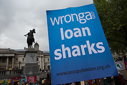 Occupy Wonga May Day. Protester from Occupy London holds a banner against the Loan company Wonga on the annual May Day march in Trafalgar Square, Central London, United Kingdom. Thursday, 1st May 2014. Picture by Daniel Leal-Olivas / i-Images