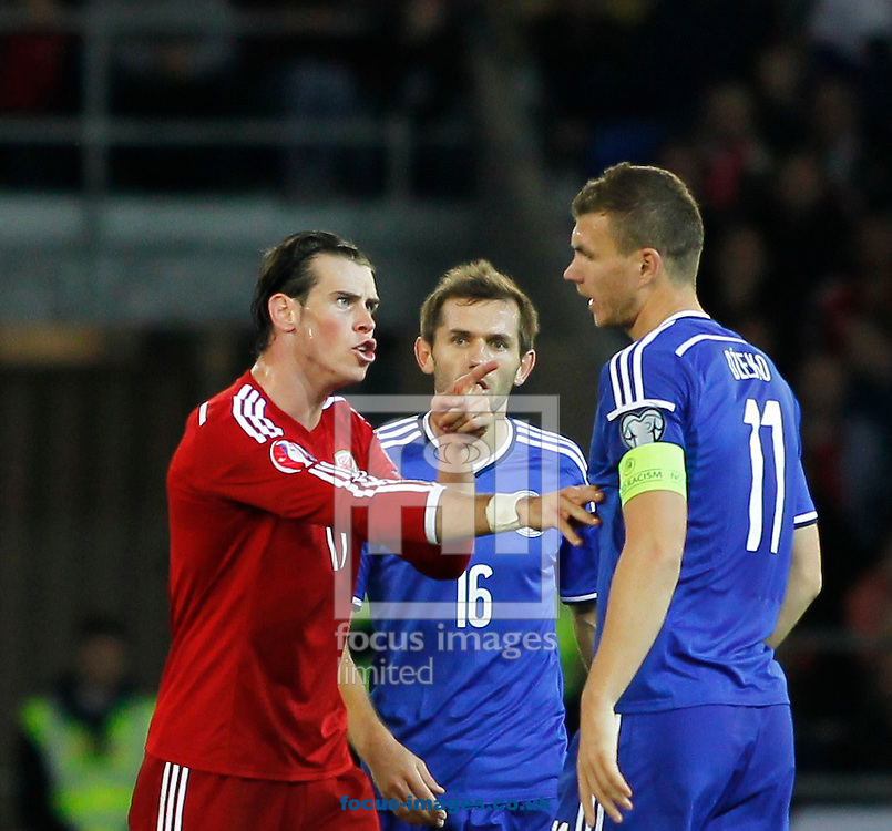 Gareth Bale of Wales and Edin Dzeko of Bosnia and Herzegovina during the UEFA Euro 2016 Qualifying match at the Cardiff City Stadium, Cardiff<br /> Picture by Mike  Griffiths/Focus Images Ltd +44 7766 223933<br /> 10/10/2014