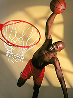 Young man dunking basketball, elevated view