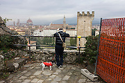 Dog and owner pause near construction netting during walk near Piazza Michelangelo to view Florence skyline