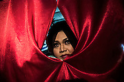 Mba Yeyen watches her friends on stage from a curtain during a show in Mojokerto, East Java, Indonesia, June 6, 2015.