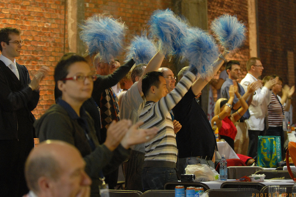 A group of recreational same-sex dancer friends who met dancing at The White Swan Club in London, England, cheer for competitors in the same-sex ballroom dancing competition with blue pom-poms during the 2007 Eurogames at the Waagnatie hangar in Antwerp, Belgium on July 13, 2007. ..The men travel to various places around the world as tourists and to watch the same-sex ballroom events. ..Over 3,000 LGBT athletes competed in 11 sports, including same-sex dance, during the 11th annual European gay sporting event. Same-sex ballroom is a growing sports that has been happening in Europe for over two decades.