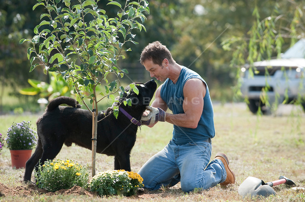 Man taking time out from gardening to pet his dog.